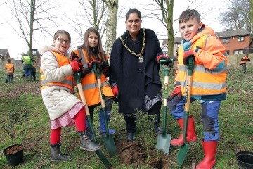 Holly Evans, Evie Marsden, Cllr Halimah Khaled MBE and Max Perry help plant a tree to improve biodiversity in Hall Om Wong Park.