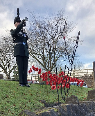 Soldier blows trumpet in front of Tommy Silhouette and poppies in Greasley