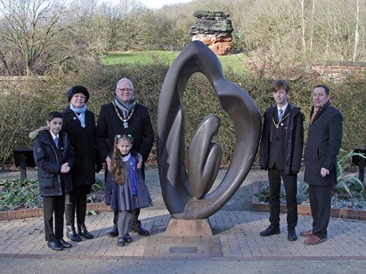 speakers at the Holocaust Memorial event gather by the Holocaust Memorial sculpture