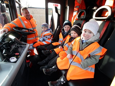 Schoolchildren sitting inside a bin lorry