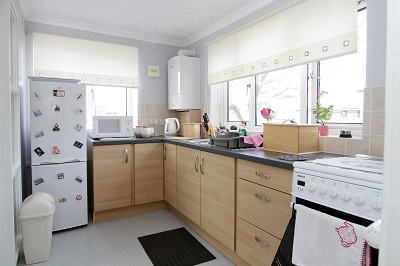 Modernised kitchen with cream coloured blinds and tiles