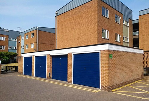 Block of garages with blue doors near blocks of housing