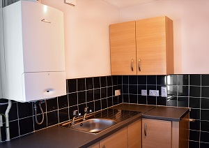 A kitchen in a Council property with a boiler, sink, cabinets and black tiles.