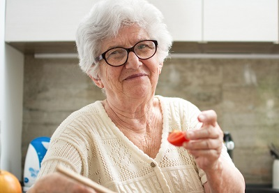 Elderley woman wearing glasses sitting in her kitchen