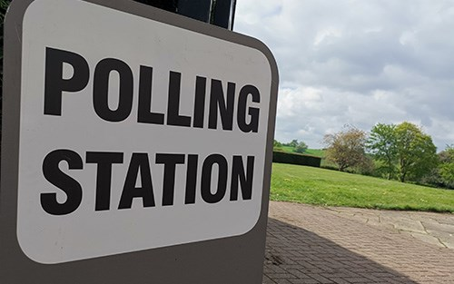 Polling Station sign next to a field