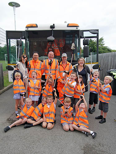 Schoolchildren with litter pickers outside a refuse vehicle