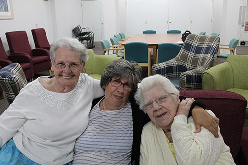 Three elderly ladies hugging on a sofa in an Independent Living Scheme's common room